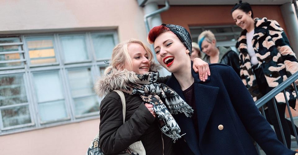 Kaksi iloista naisopiskelijaa, taustalla muita opiskelijoita