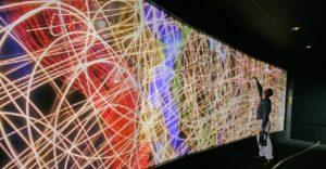 Mies tarkastelee visualisoitua dataa suurelta näytöltä