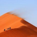 Ihmisiä vaeltamassa kohti vuoren huippua hiekka-aavikolla