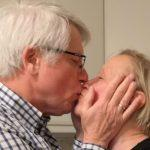 An elderly couple kissing