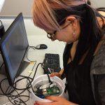 Artikkelin pääkuva: Toisen vuoden biotalouden insinööri -opiskelija Jenni Alitalo-Nieminen kasaa tiiminsä kanssa etäseurannan ratkaisua, jota tiimi pääsee kesätyönään testaamaan aitoon kohdeympäristöön.