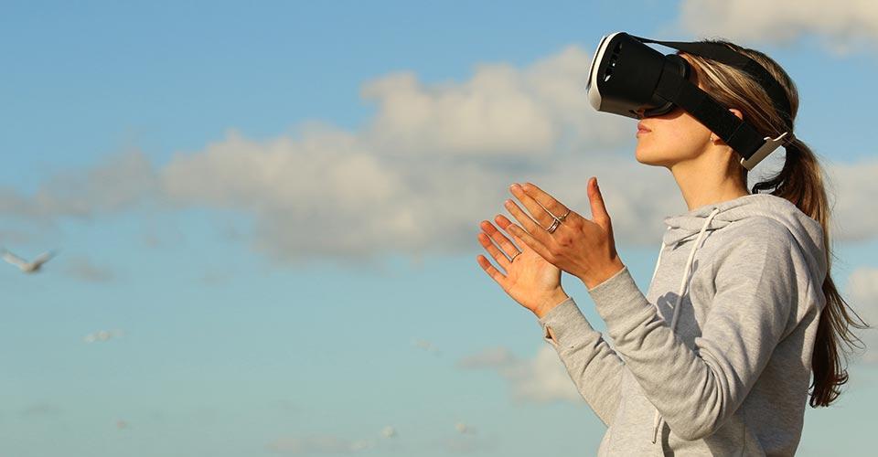 Nainen seisoo vr-lasit päässä, taustalla taivasta.