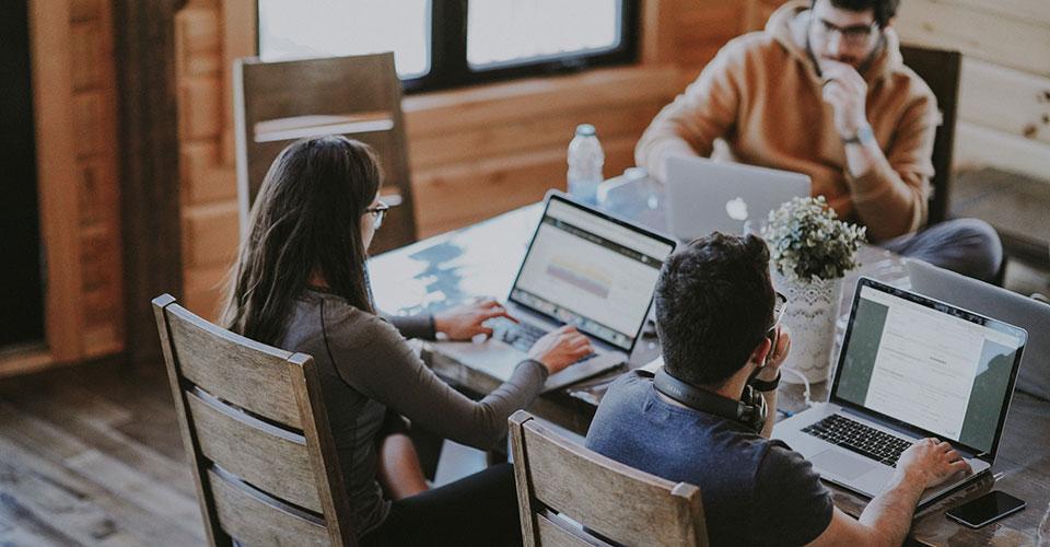 henkilöt työskentelevät pöydän äärellä kannettavilla tietokoneilla